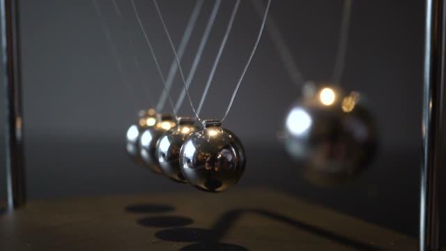 närbild video av metall newton vagga swinging på grå bakgrund - fysik bildbanksvideor och videomaterial från bakom kulisserna