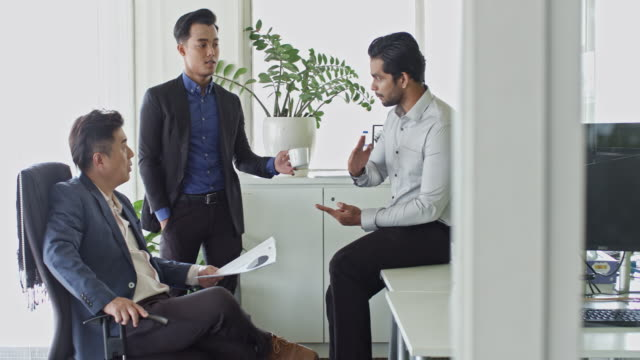 Close-up video of three multi-ethnic Malaysian businessmen brainstorming at office Close-up video of three multi-ethnic Malaysian businessmen brainstorming at office. office cubicle stock videos & royalty-free footage