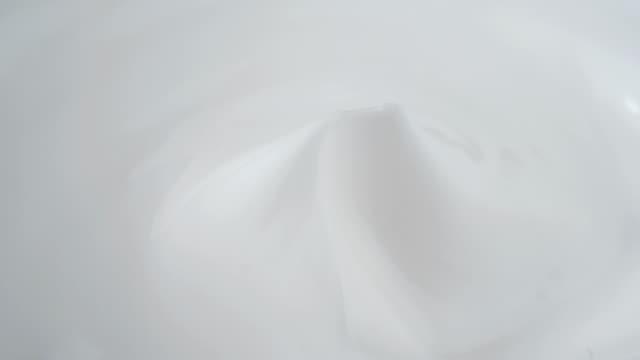 クローズアップビデオ撮影、ホワイトスキンクリームが回転、美容トリートメントコンセプト - くるくる回る点の映像素材/bロール