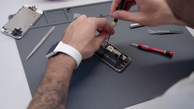 close-up video showing process of mobile phone repair - pinze attrezzo manuale video stock e b–roll