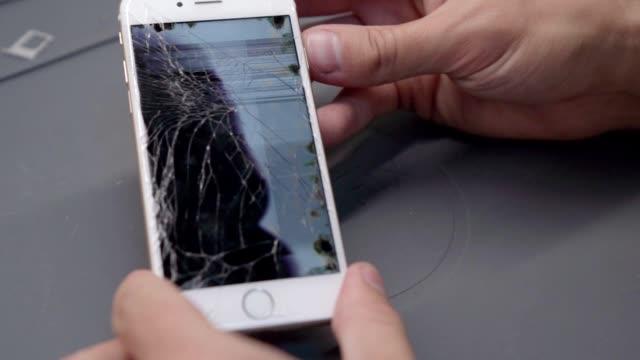 närbild-video som visar processen för mobiltelefon reparation - trasig bildbanksvideor och videomaterial från bakom kulisserna