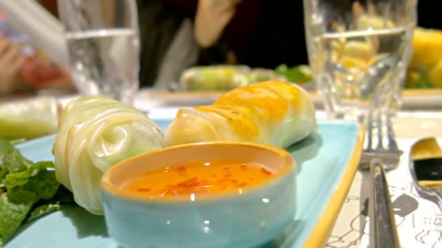 stockvideo's en b-roll-footage met close-up vietnamees saus en lente rollen nem op tafel in restaurant - pepernoten