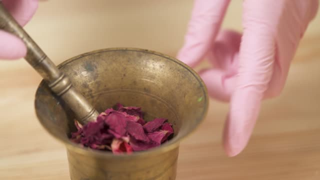 Close-up view, a girl grinds dried rose petals in powder in a copper mortar with pestle. Close-up view, a girl grinds dried rose petals in powder in a copper mortar with pestle. mortar and pestle stock videos & royalty-free footage