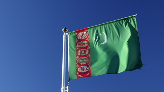 Close-up view flag of Turkmenistan waving in the wind on a blue sky background without clouds, dark green leaf with five white five-pointed stars, white crescent, vertical stripe with Gulus - patterns official Turkmenistan flag turkmenistan stock videos & royalty-free footage
