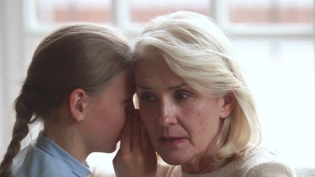 primo piano vista nipotina sussurrando segreto all'orecchio della nonna - ear talking video stock e b–roll