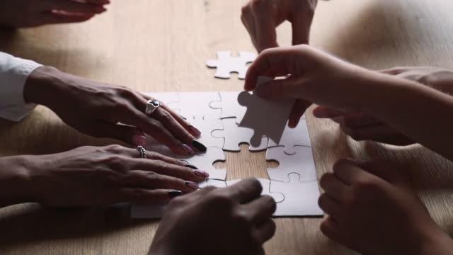 stockvideo's en b-roll-footage met close-up bekijk multi-etnische mensen die stukjes puzzel puzzels verbinden - legpuzzel