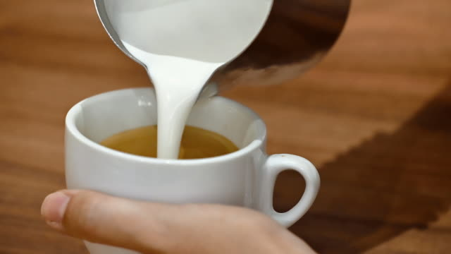 Close-up view of a barista demonstrating the art of pouring and preparing a cup of coffee. Making latte art. High quality FullHD footage.
