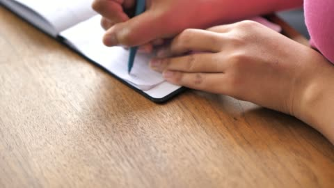 vídeos y material grabado en eventos de stock de una vista de primer plano de una mujer afroamericana de raza mixta negra con una camisa rosa sentada en una mesa de comedor de madera y escribiendo una nota en su bloc de notas de papel con un bolígrafo con las manos y el pecho en el marco. - miembro humano