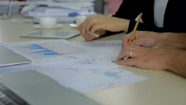 Closeup view of a colleagues financier, trader using a pencil to draw a line on a graph of securities trading. discussing data video