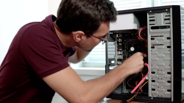Closeup view of a concentrated computer service worker in glasses fixing a broken computer in the office and upgrading computer hardware. Support team. Computer maintenance. Shot in 4k video