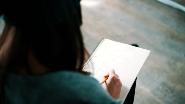 Vista de cerca de un estudiante tomando notas durante las charlas. Vista desde la parte posterior. Rodada en 4k. - vídeo