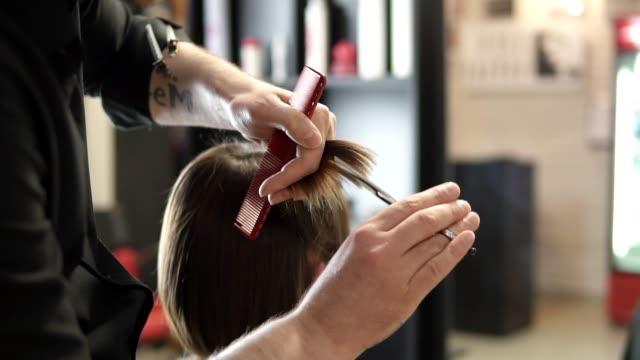 美容師のクローズ アップ ビューは、はさみで髪をカットを手します。若い女性が彼女の髪を得ることは、ヘアサロンに身を包んだ。仕事で美容院。美容サロン。スローモーションで撮影します。 ビデオ