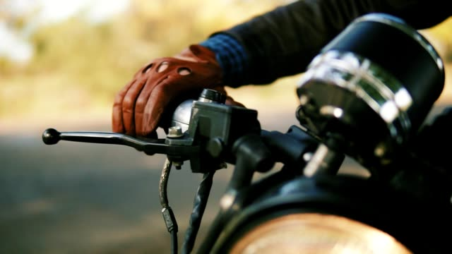 Closeup view of a man's hand in brown leather mitts starting the engine. Slowmotion shot