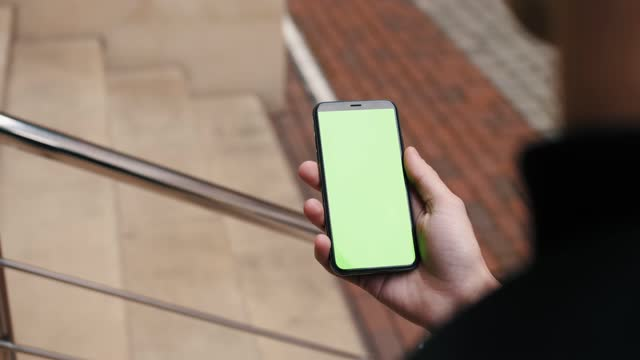 Close-up view of a person holding a smartphone swiping pages on mockup green screen outdoor