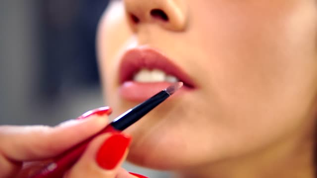 Closeup view of a professional makeup artist applying lipstick on model's lips working in beauty fashion industry. Closeup view of an artist's hand using two special brushes video