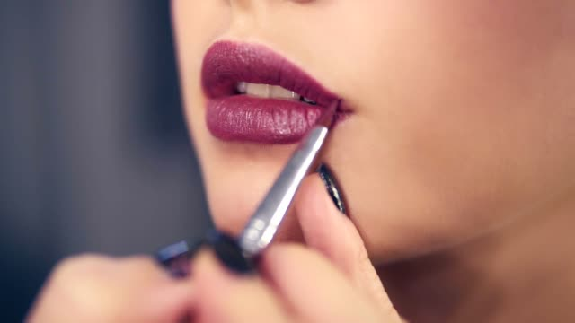 closeup view of a professional makeup artist's hand using special brush to apply lipstick or lips gloss on model's lips working in beauty fashion industry. slowmotion shot - make up stock videos & royalty-free footage
