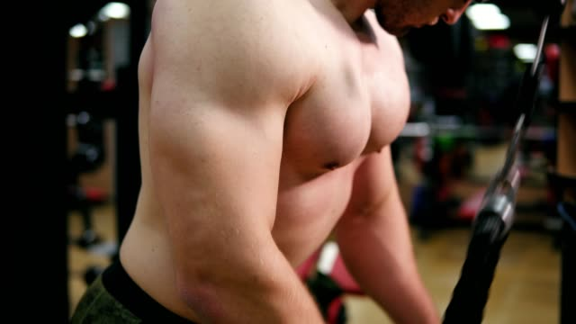 Closeup view of a shirtless attractive man's hands while training triceps using crossover in the gym. Muscular body, closeup view. Shot in 4k video