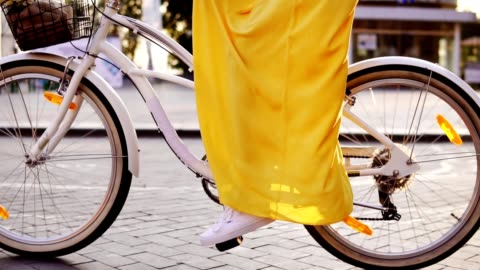 detailansicht der eine weiße stadt fahrrad räder durchdrehen. citybike mit einer glocke, korb und blumen. nicht erkennbare frau reiten ein city-bike in den frühen morgenstunden. steadicam gedreht. slowmotion - gelb stock-videos und b-roll-filmmaterial