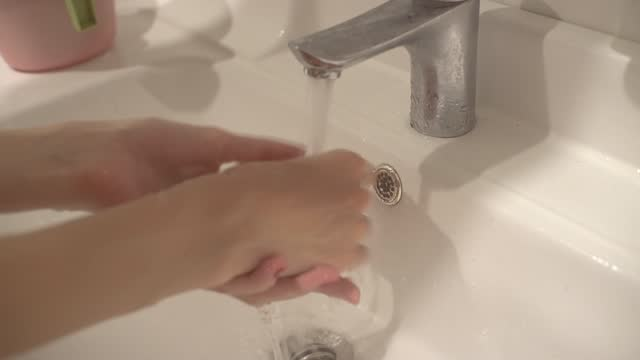 Closeup view of a woman washing hands in the bathroom. A woman washes her hands in the wash basin.