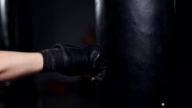 closeup view of a woman's hand in boxing gloves punching a bag in a boxing club. slowmotion shot - sacco per il pugilato video stock e b–roll