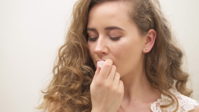 A close-up view of a young beautiful girl applying hygienic natural lip balm on her lips