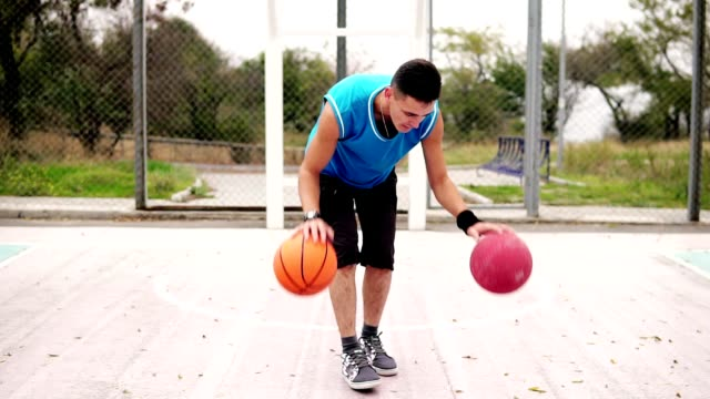 Closeup view of a young man practicing basketball on the street court. He is playing with two balls simultaneously. Slowmotion shot video