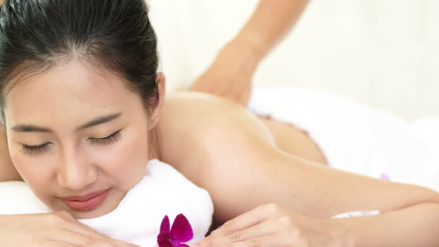 Closeup view of a young woman with oiled skin having thai massage of her back and shoulders in spa club. video