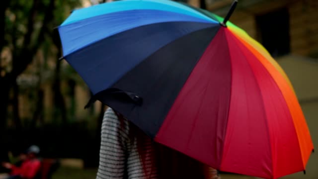 vídeos de stock e filmes b-roll de closeup view of an open spinning colourful rainbow umbrella in female hands. slowmotion shot - guarda chuva