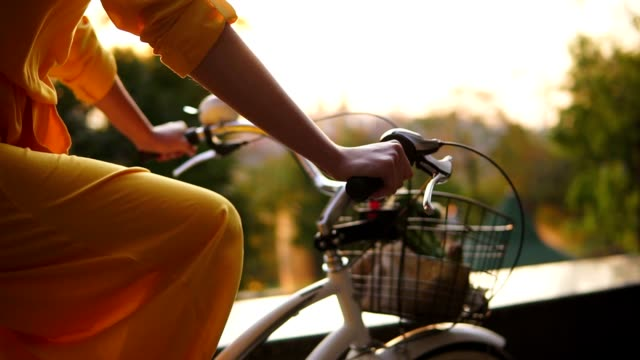 Closeup view of an unrecognizable woman's hands holding a handlebar while riding a city bicycle with a basket and flowers. Lens flare during early moning. Sun is rising. Steadicam shot video