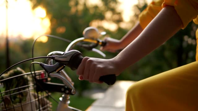 Closeup view of an unrecognizable woman's hands holding a handlebar while riding a city bicycle with a basket and flowers. Lens flare during early moning. Sun is rising. Woman in yellow dress video