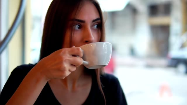 Closeup view of attractive young woman dreaming with cup of hot coffee sitting by the window in the coffee shop. Break after long busy day. Relaxation with a warm cup of tea video