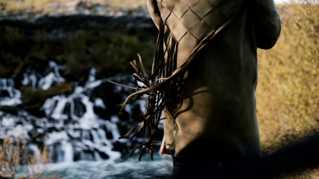 Close-up view of Barnafoss waterfall in Iceland and female back. Fringe from jacket of young woman waves on wind video
