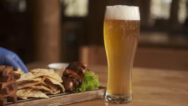 primo piano vista di birra e snack. un bicchiere con birra e snack su un piatto su tavolo di legno. il cameriere mette un piatto di patatine, crostini, pollo e salsa - antipasto video stock e b–roll