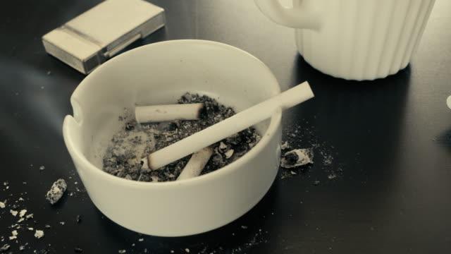 närbild av brinnande cigarett på askkopp - coffe with death bildbanksvideor och videomaterial från bakom kulisserna
