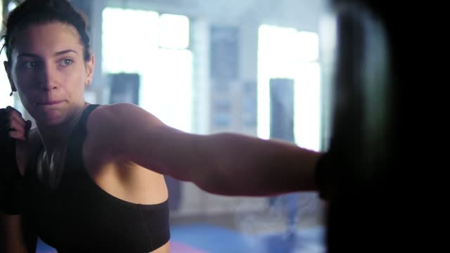 Closeup view of caucasian female boxer hitting the boxing bag with her hands in gloves in the gym with smoke. Tough power training of a female kickboxer