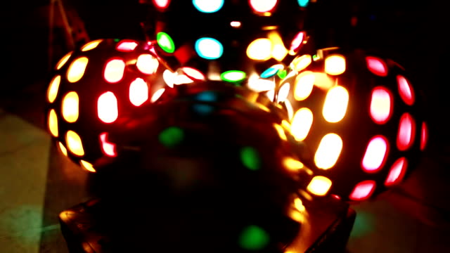 Close-up view of colored light disco ball twisting. Colored show at the disco club party. Rays of the scene light video