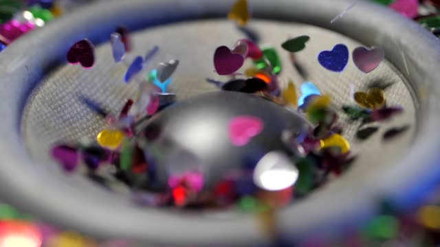 Close-up view of decorative small colorful hearts dancing on sub-woofer. Speaker moving from loud music. Christmas, New Year or Valentine's concept. Funny background video