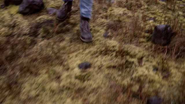 Close-up view of female foot in boots. Young woman walking through the bogs with moss, exploring the nature alone