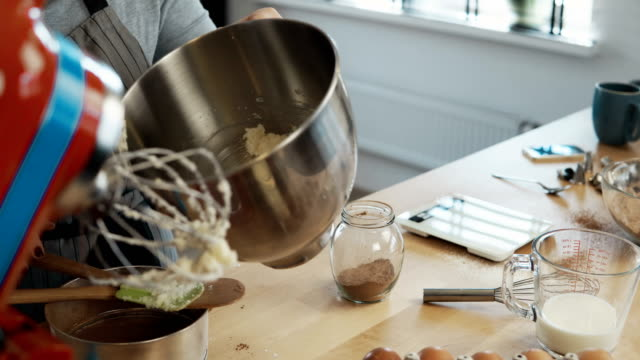 Close-up view of female hand putting the batter in the bowl. Young woman blending ingredients, using mixer for this video