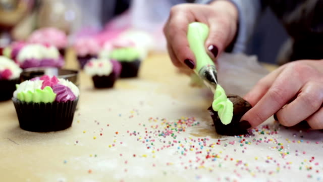 Close-up view of female hands decorating the chocolate cupcake, using pastry bag with colored cream video