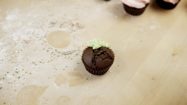 Close-up view of female hands decorating the chocolate cupcake with colored cream, using pastry bag for this video