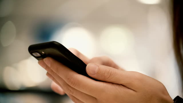 Close-up view of female hands holding smartphone, using the touchscreen technology. Young woman typing on the screen video