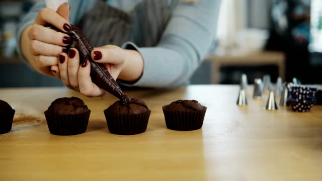 Close-up view of female hands puts the cream from pastry bag on chocolate cupcakes. Young woman cooking the muffins video