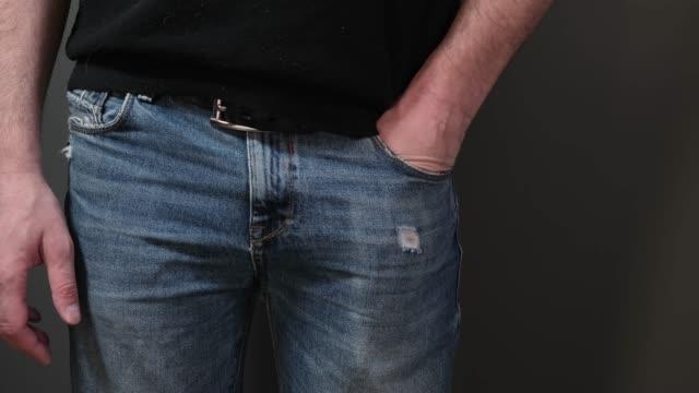 närbild syn på handen dra ut en smart telefon av bakre jeans ficka. närbild - byxor bildbanksvideor och videomaterial från bakom kulisserna