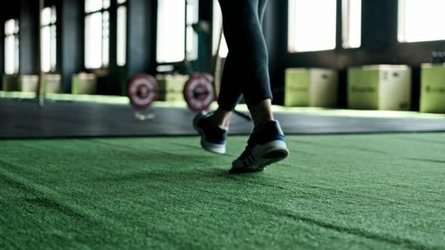 stockvideo's en b-roll-footage met close-up weergave van de benen van jonge fit vrouw het invoeren van fitnessclub. tracking shot - paardenstaart haar naar achteren