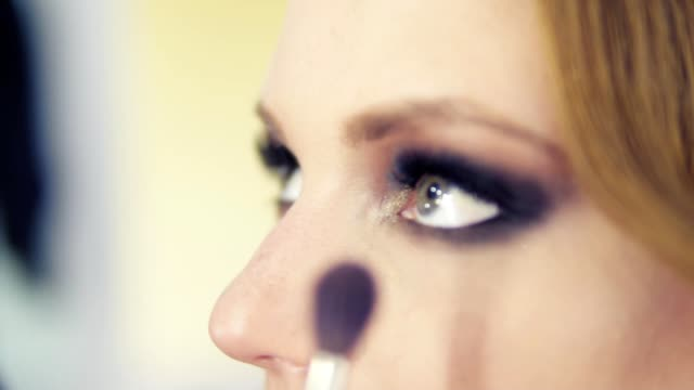 stockvideo's en b-roll-footage met close-up weergave van make-up artiest oogschaduw bij ooglid met behulp van make-up borstel toe te passen. professionele make-up. tikje schot - oogschaduw