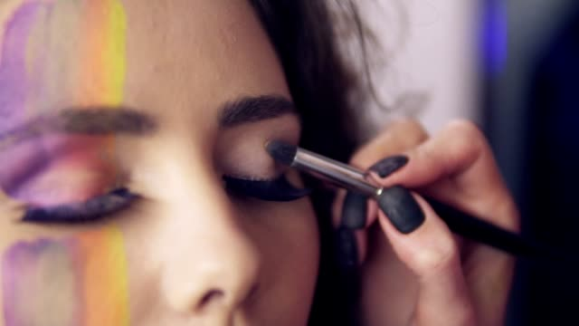 Closeup view of makeup artist makes models eye makeup with false eyelashes. Model with false lashes and face art painting preparing to the fashion show. Slowmotion shot. video