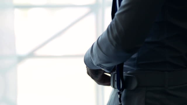 Close-up view of male hands buttons braces in front of window. Young businessman getting ready for a work in the morning video