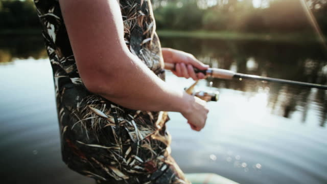 Close-up view of male hands holding the fishing rod with spinning reel. Young man catching the fish alone video
