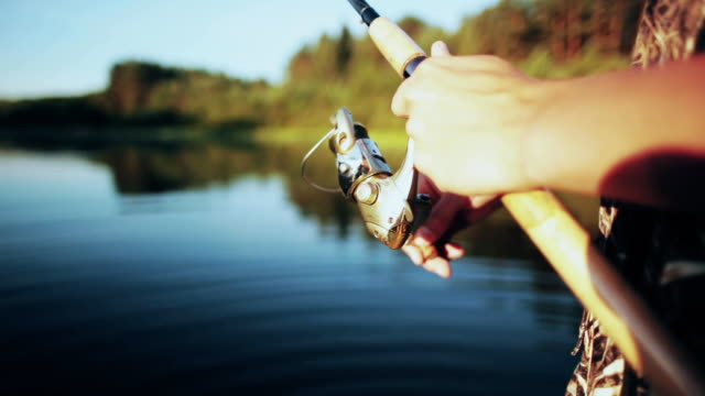 Close-up view of male hands holding the fishing rod. Young Fisher man twisting the rod with spinning reel video